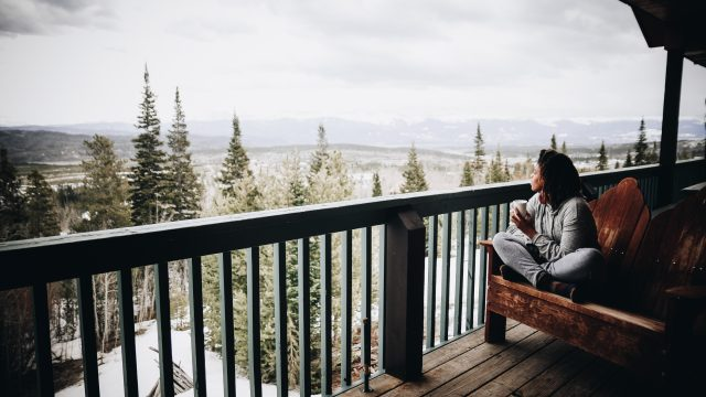 Woman Sitting Outside on Bench Enjoying Snowy View