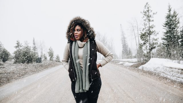 Woman Standing In Middle of Road in Snowy Weather