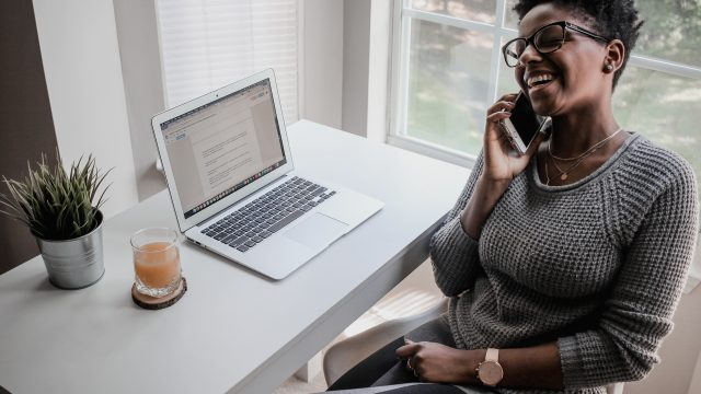 Woman Laughing While on Phone In Home Office